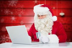 Le père noël faisant des achats en ligne avec la carte de crédit sur l'ordinateur portable Photos stock