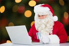 Le père noël faisant des achats en ligne avec la carte de crédit sur l'ordinateur portable Images stock
