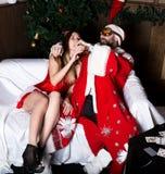 Le père noël ivre avec la femme sexy d'infirmière féminine en eau-de-vie fine potable de costume de carnaval Photos stock