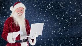 Le père noël jugeant un ordinateur portable combiné avec la neige en baisse clips vidéos