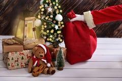 Le père noël mettant secrètement le sac à cadeau sous l'arbre de Noël Image stock