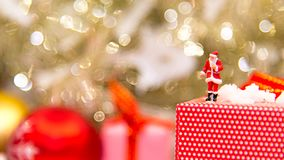 Le père noël miniature se tenant avec de grandes boîtes actuelles en tant que Joyeux Noël image libre de droits