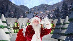 Le père noël ondulant devant les maisons décorées combinées avec la neige en baisse clips vidéos