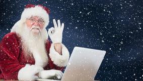 Le père noël s'asseyant devant son ordinateur portable combiné avec la neige en baisse banque de vidéos
