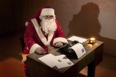 Le père noël s'asseyant par un bureau Photos libres de droits