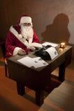 Le père noël s'asseyant par un bureau Images libres de droits