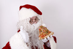 Le père noël souriant et mangeant de la pizza Photos stock