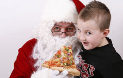 Le père noël souriant et mangeant de la pizza Photo stock