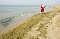 Le père noël sur le bord de la mer Photographie stock libre de droits