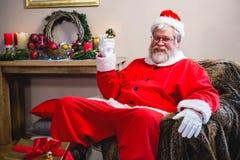 Le père noël tenant un cadeau et s'asseyant sur le sofa à la maison Photos stock