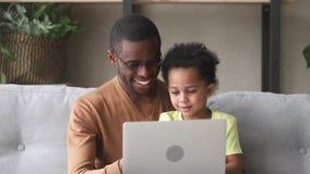 Le père noir heureux enseignent le fils d'enfant à lire l'ordinateur portable d'utilisation banque de vidéos