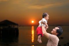 Le père partageaient un bébé pour supporter et la vue de coucher du soleil sur l'evenin Images stock
