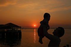Le père partageaient un bébé pour supporter et la vue de coucher du soleil sur l'evenin Image libre de droits