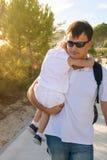 Le père porte dedans sa fille de bras dans la belle lumière Photographie stock libre de droits