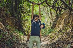 Le père porte son fils dans un bébé que le transport augmente dans le touriste de forêt ramène un enfant sur le sien en forme de  photo stock