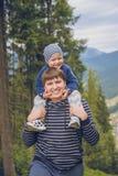 Le père ramènent le fils sur le sien photographie stock