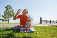 Le père sérieux et sa petite fille gonflent ensemble des bulles Images libres de droits