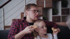Le père sérieux repose avec attrayant petite fille sur le sofa au salon clips vidéos