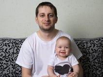 Le père tient le bébé dans des ses bras, l'enfant rit véritablement photographie stock