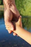 Le père tient l'enfant par une main sur la promenade Image libre de droits
