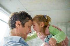 Le père tient la petite fille sur des mains Image stock