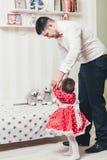 Le père tient une fille d'un an par la main et l'aide à aller Le papa et la petite fille jouent dans la chambre photographie stock