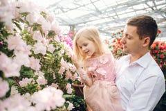 Le père tient une fille de bébé dans le jardin de floraison Image stock