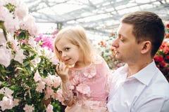 Le père tient une fille de bébé dans le jardin de floraison Image libre de droits