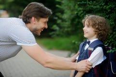 Le père voit sa premier-niveleuse de fils à l'école Photo stock