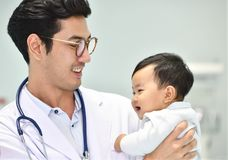 Le pédiatre asiatique prend soin de bébé Photographie stock libre de droits