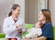 Le pédiatre mûr de prescrit au bébé nouveau-né le medicatio photo libre de droits