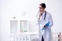 Le pédiatre masculin d'homme près du lit de bébé préparant pour examiner image libre de droits