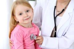 Le pédiatre prend soin de bébé dans l'hôpital La petite fille est examinent par le docteur par le stéthoscope Soins de santé Photographie stock
