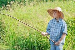 Le pêcheur à la ligne a concentré le garçon observant après que flotteur fait main de canne à pêche sur l'eau Photos stock