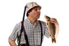 Le pêcheur aîné avec la canne à pêche et sien attrapent Image stock