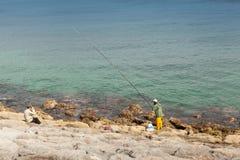 Le pêcheur arabe avec une longue tige se tient sur la côte de l'Océan Atlantique Image libre de droits