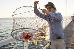 Le pêcheur attirant fier montrant des poissons et les crabes des captures de filet de panier souriant en mer accouplent le couche Images libres de droits