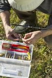 Le pêcheur choisit une amorce en caoutchouc de la boîte image stock