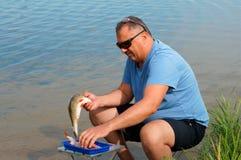 Le pêcheur coupe les poissons sur le rivage, un homme nettoie les poissons photographie stock