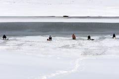 Le pêcheur désireux pêche des poissons pendant l'hiver dans le trou fait dans la glace couvrant le lit de rivière À côté de la fo images libres de droits