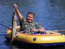 Le pêcheur dans le bateau avec un brochet photo stock