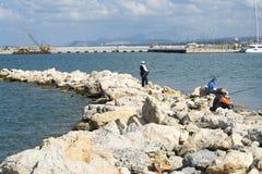 Le pêcheur dans un gilet et une pêche de chapeau sur des pierres en mer ondule Images libres de droits