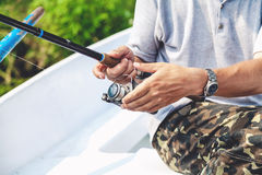 Le pêcheur de mains tenant la canne à pêche et la poignée de bobine est tourné photo libre de droits