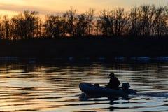 Le pêcheur en le bateau sur la rivière Photos stock