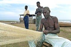 Le pêcheur ghanéen supérieur s'assied pour réparer le filet Images libres de droits