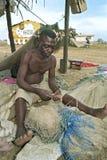 Le pêcheur ghanéen supérieur s'assied pour réparer le filet Image stock