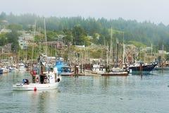 Le pêcheur guide son bateau dans le port image libre de droits