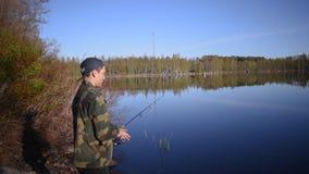 Le pêcheur, jeune homme, jette des articles de pêche dans le lac banque de vidéos