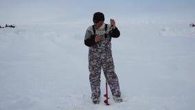 Le pêcheur masculin On The Ice forant un trou pour la glace visse la pêche banque de vidéos
