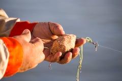 Le pêcheur met l'amorce sur un crochet de canne à pêche Photo stock
